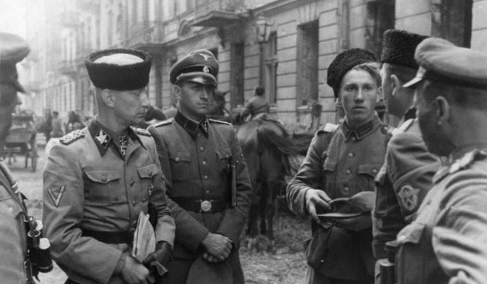 """SS-Gruppenführer Heinz Reinefarth (pierwszy od lewej) w czapce """"kubance"""" oraz żołnierze 3 Pułku Kozaków płk. Jakuba Bondarenki – okolice ul. Wolskiej w Warszawie"""