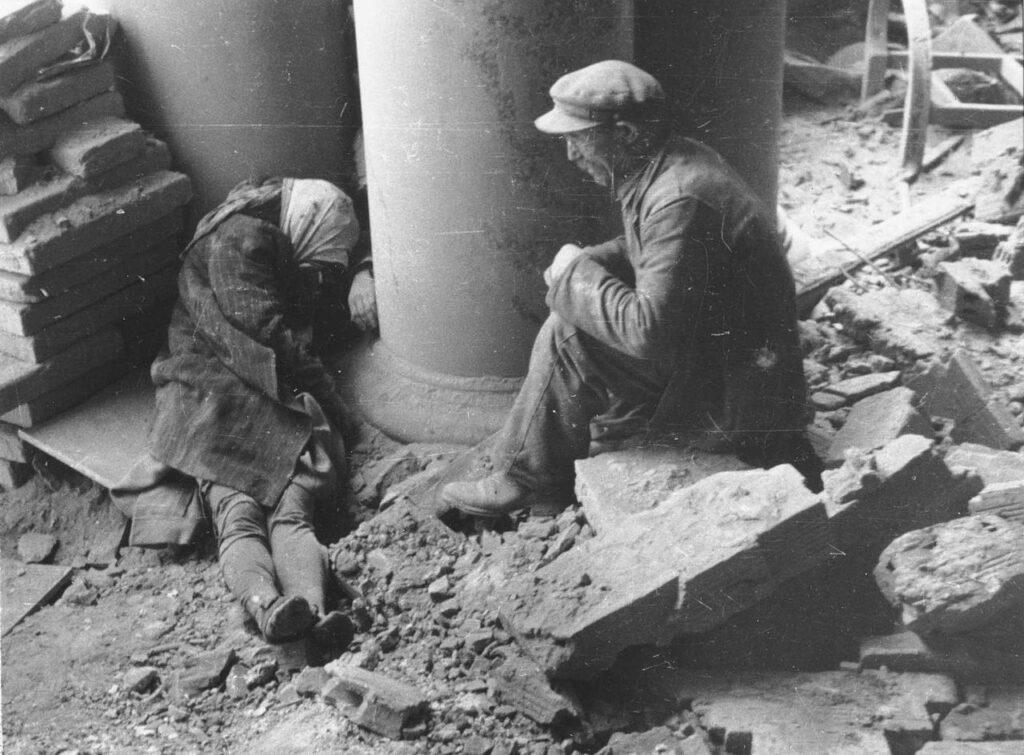 """Powstanie warszawskie - Po nalocie odkopany spod gruzów mężczyzna siedzi przy zwłokach kobiety przy wejściu do """"Adrii"""" na ul. Moniuszki 10."""